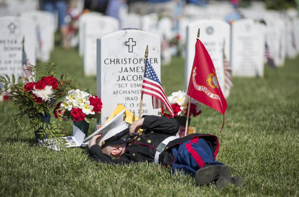 Christian Jacobs, 4, of Hertford, NC, lies on the grave of his father, Christian James Jacob, during Memorial Day celebrations at Arlington National Cemetery in Arlington, Virginia May 25, 2015. REUTERS/Joshua Roberts TPX IMAGES OF THE DAY